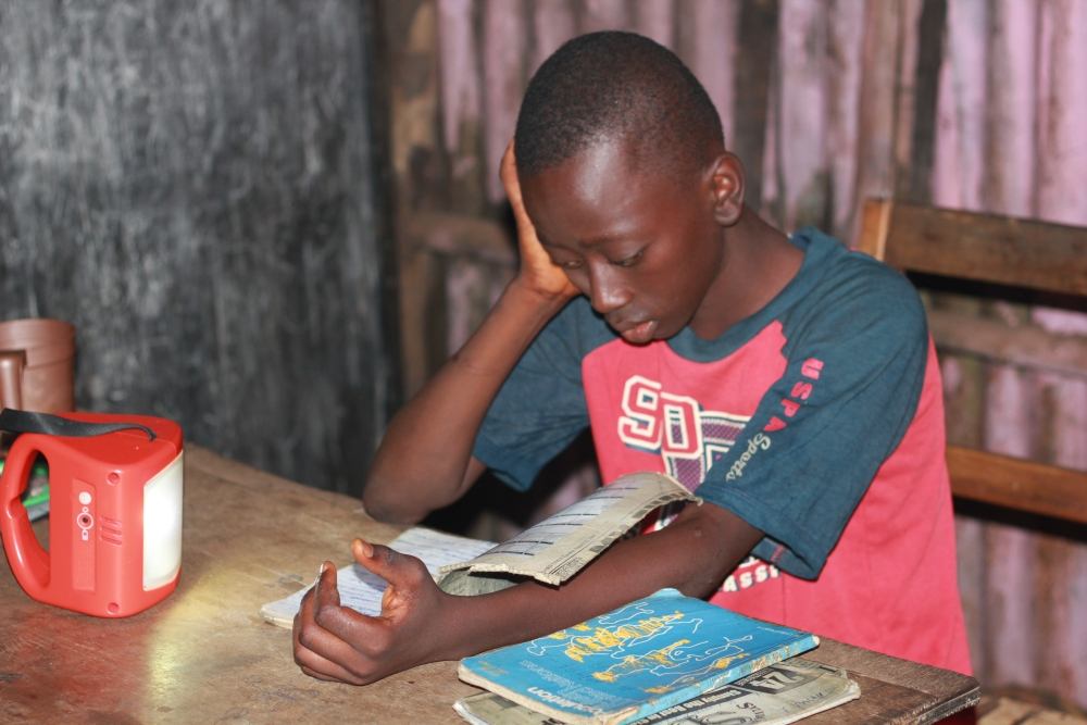 Child studying with the aid of a solar lantern