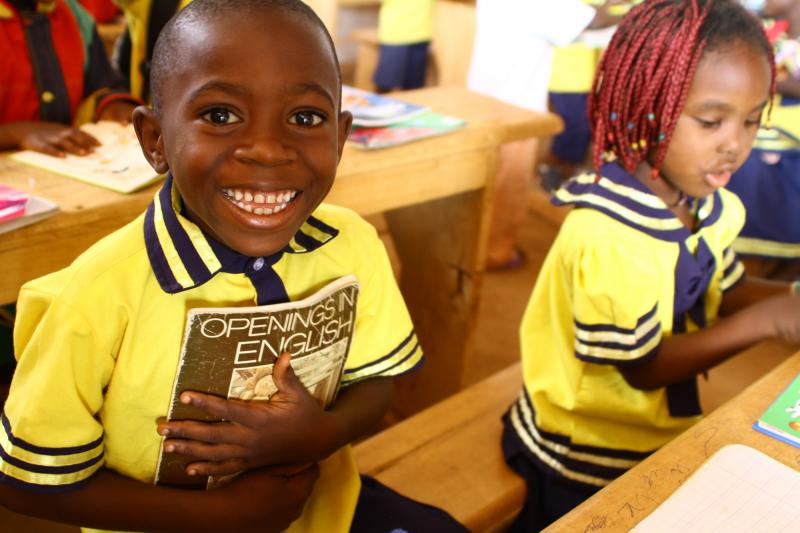 Boy reading a book in classroom in Cameroon